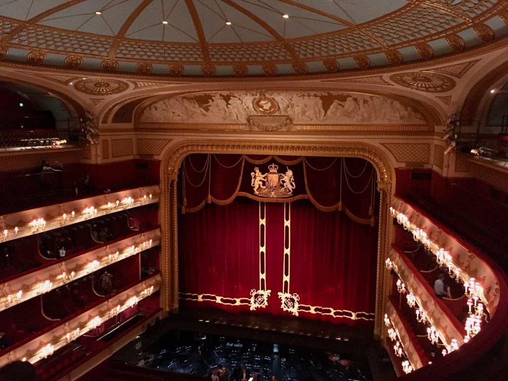 The photo shows the stage in the Royal Opera House, which is very grand and opulent.